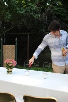 Calvin lights the candles just before the party starts. For the communal table, keep things simple. Small floral centerpieces and candles on a white tablecloth give the perfect summer feel.